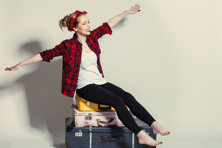 woman sits on retro suitcases