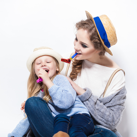 noisemaker: A gorgeous young mother blowing on a party favor while hugging daughter