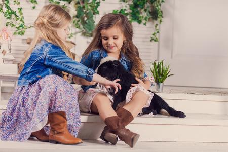 bebes niñas: Niñas que juegan con una cabra bebé en un porche de la casa Foto de archivo