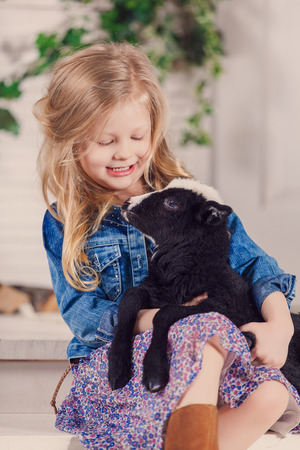yeanling: Little girl playing with a baby goat on a house porch Stock Photo