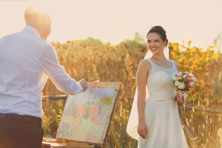 newly married: Groom paints a portrait of his beloved bride. Newly married wedding couple in a vintage setting. Sunset