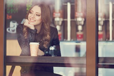 Jonge vrouw het drinken koffie zit binnen in de stedelijke cafe. Cafe stad lifestyle. Casual portret van tienermeisje. Afgezwakt Stockfoto