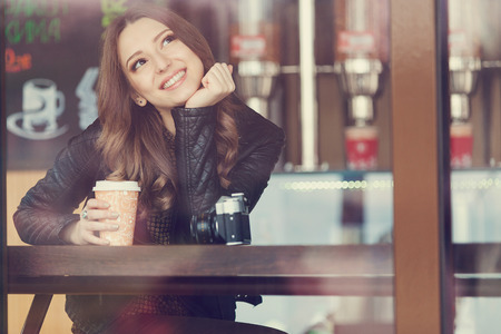 Young woman drinking coffee sitting indoor in urban cafe. Cafe city lifestyle. Casual portrait of teenager girl. Toned photo