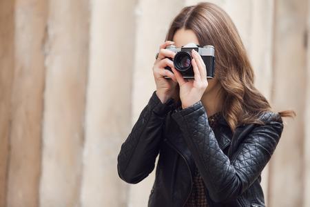 chicas sonriendo: Retrato de una joven turista bastante tomar fotograf�as con la c�mara retra de la vendimia Foto de archivo