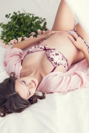pregnant lingerie: Home portrait of pregnant woman in lingerie Stock Photo