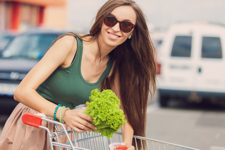 wit: Young woman wit shopping cart outdoor Stock Photo
