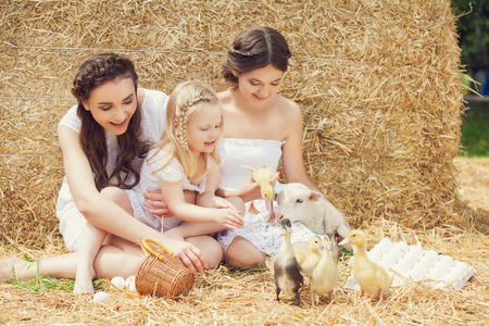Beautiful girls with little sister relaxing in the straw at farm Reklamní fotografie