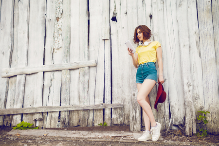 Funny Hipster Girl over white old wooden wall, hipster outfit Going Crazy at tropical island.Trendy Casual Fashion Outfit in summer, spring.Toned Photo, Copy Space. Фото со стока