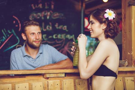 mujeres atractivas hermosas en el bar de la playa tropical. Muchacha hermosa que disfruta de cócteles exterior. Las mujeres caucásicas sonriente feliz en la playa.