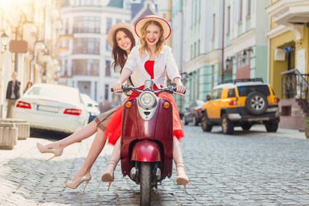 Two beautiful girls in urban background smiling with old scooter Imagens - 58119160