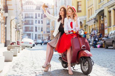 mujeres fashion: Dos muchachas hermosas en fondo urbano que sonríe con la vespa vieja Foto de archivo