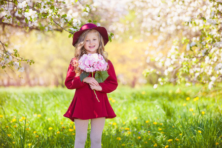 girl in burgundy dress: Beautiful little blonde girl in hat and burgundy dress. In her hand bouquet. Summer sunny day, lots of greenery and flowers Stock Photo