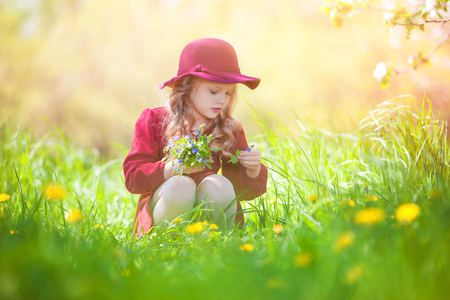 girl in burgundy dress: Beautiful little girl picking flowers in a meadow. Summer sunny day, lots of greenery and flowers.Blonde girl in burgundy dress.