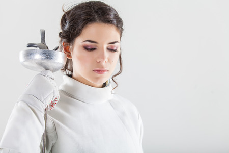 fencing sword: Portrait of woman wearing white fencing costume practicing with the sword