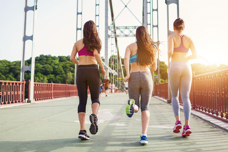outdoor training: Three sportive pretty women enjoying their run - on city bridge at sunset. Sporty friends portrait