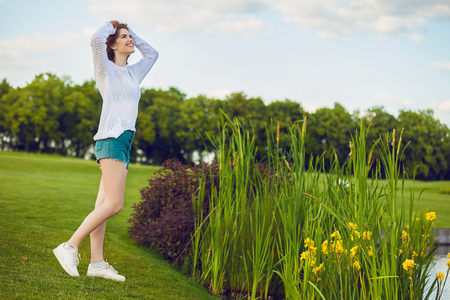 Outdoor photo of young woman near the pond. Beautiful tender woman with red hair posing in summer park. Imagens