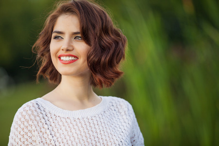 Outdoor photo of young woman. Beautiful tender woman with red hair posing in summer park.