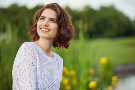 Outdoor photo of young woman near the pond. Beautiful tender woman with red hair posing in summer park