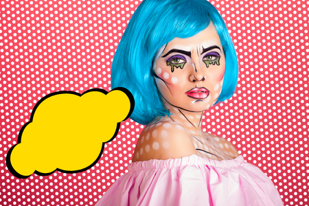 Photo of young woman with speech bubble and professional comic pop art make up. Creative beauty style.