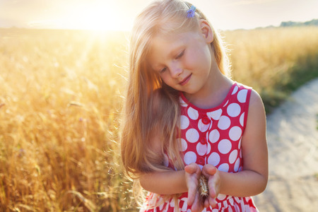 Little girl on a wheat field in the sunset.