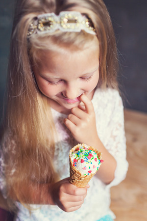Kid girl eating tasty ice cream Imagens