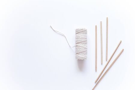 Tools and materials for macrame weaving over white surface. Cotton ropes and sticks from the river, grinded by water. Flat lay, top view. Step by step instructions for macrame weaving. Step 1 DIY.