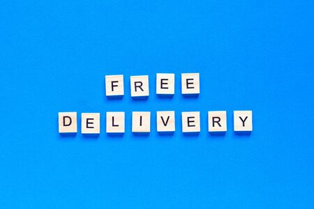 Free delivery lettering in wooden letters on  blue