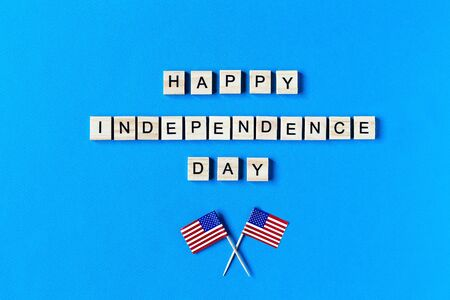 happy Independence Day inscription in wooden letters on a blue background. Happy Independence Day. The 4th of July. USA Independence day. American flags. copy space. top view