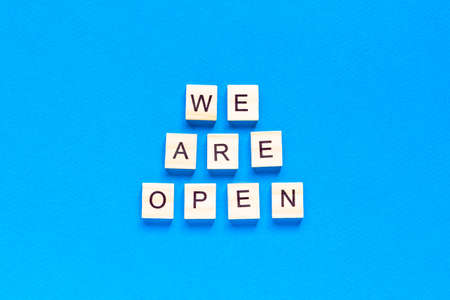 We are open. Wooden cubes with a text message We are open on a blue background. The view from the top. Flat layout. An office, cafe, or store welcomes guests after a coronavirus outbreak. The end of quarantine.
