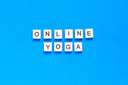 The word ONLINE YOGA written in wooden letterpress type on a blue background. top view. flat layout. Фото со стока