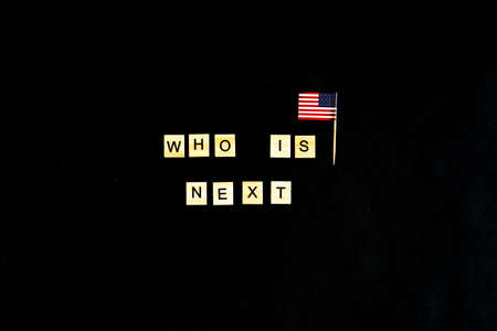 The phrase Who is the next American President - with an American flag in the background. A new election race in the United States. Primary. Candidates. Politics. Government. Force. flatlay, top view Фото со стока