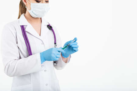 A young nurse in a mask opens a syringe on a white background in a white coat, to make a vaccination, an injection. The concept of vaccination and protection against influenza, from avid, copy space