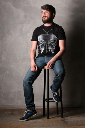 Bearded man in T-shirt with butterfly sitting on a bar stool