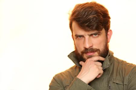 Bearded guy in khaki jacket holding his chin Stock Photo