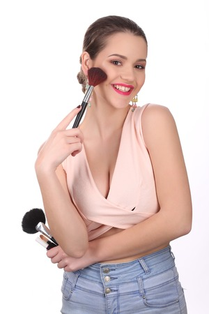 Smiling girl in pink top posing with cosmetics