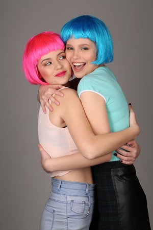 wigs: Smiling girls in colorful wigs hugging