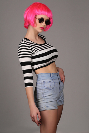 cheekbones: Teen with circle sunglasses and pink hair posing, pink wig, cosplay, high fashion look, perfect make-up, beautiful girl, smiling girl, isolated, looking into the camera, model in studio, close up, gray background Stock Photo