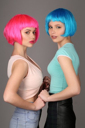 wigs: Girls in colorful wigs holding hands and posing, blue wig, friendship, high fashion look, perfect make-up, cute friends, smiling girl, looking into the camera, model in studio, close up, gray background