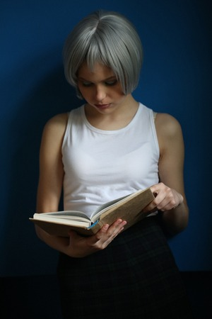 cheekbones: Lady with silver hair reading a book and candles, silver wig, cosplay, high fashion look, perfect make-up, beautiful girl, smiling girl, isolated, looking into the camera, model in studio, close up, blue background