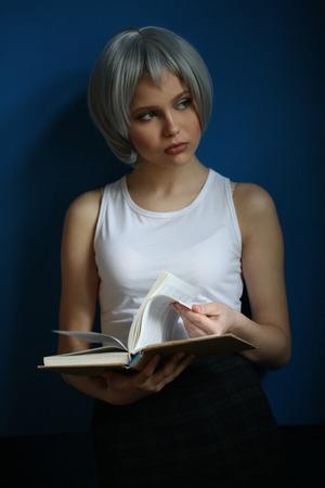cheekbones: Teen with silver hair leafing through the book Stock Photo