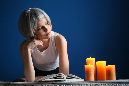 Girl in silver wig posing with book and candles, silver wig, cosplay, high fashion look, perfect make-up, beautiful girl, smiling girl, isolated, looking into the camera, model in studio, close up, blue background