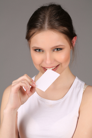 Teen lady in biting slip of paper Stock Photo