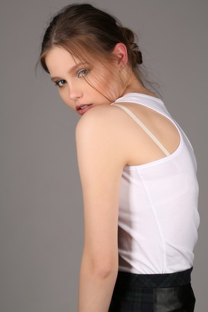 white singlet: Lady in white singlet standing profile, high fashion look, perfect make-up, beautiful girl, smiling girl, isolated, looking into the camera, clear skin,big lips, model in studio, close up, gray background