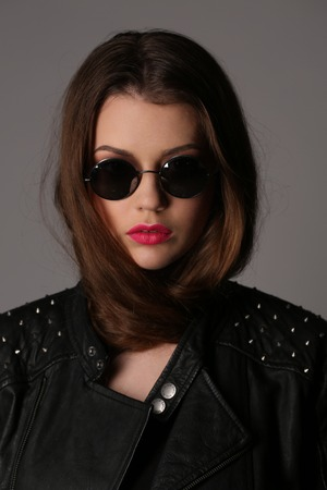 collarbone: Girl in a studded leather jacket and circle sunglasses, high fashion look, perfect make-up, beautiful girl, smiling girl, isolated, looking into the camera, clear skin,big lips, model in studio, close up, white background Stock Photo