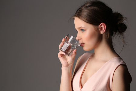 vasos de agua: Lady in pink top drinking water, healthy people, high fashion look, perfect make-up, beautiful girl, smiling girl, isolated, clear skin,big lips, model in studio, close up, gray background