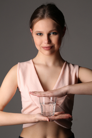 collarbone: Girl in pink top holding glass of water, healthy people, high fashion look, perfect make-up, beautiful girl, smiling girl, isolated, clear skin,big lips, model in studio, close up, gray background Stock Photo