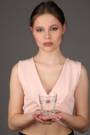 collarbone: Model in pink top holding glass of water Stock Photo
