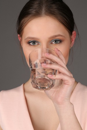 collarbone: Girl wearing pink top drinking water, healthy people, high fashion look, perfect make-up, beautiful girl, smiling girl, isolated, clear skin,big lips, model in studio, close up, gray background