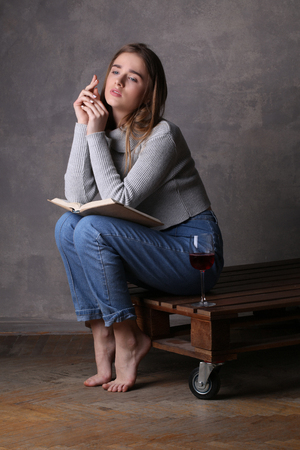 pretty eyes: Model posing with book and glass of wine, girl with wineglass, high fashion look, sitting girl, beautiful girl, blonde girl, isolated, model in studio, girl wearing jeans and sweater, long hair, gray background