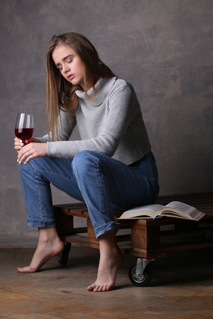 girl with gray eyes: Sitting girl with closed eyes holding glass of wine, girl with wineglass, high fashion look, sitting girl, beautiful girl, blonde girl, isolated, model in studio, girl wearing jeans and sweater, long hair, gray background